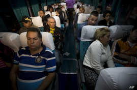 Cuban migrants wait on a bus in Ciudad Pedro De Alvarado, Guatemala, at the border with El Salvador, Wednesday, Jan. 13, 2016, as they continue on their journey to the United States.