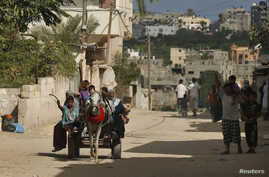 Palestinians, who fled their homes in the northern border town of Beit Lahiya, ride a horse cart as they make their way to stay at a United Nations-run school, in the northern Gaza Strip, July 14, 2014.