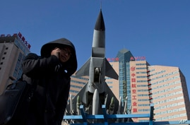A Chinese man uses his mobile phone near a replica of a Chinese made fighter jet displayed in Beijing, China, Nov. 27, 2013.