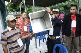 Electoral workers show an empty box before the opening station for voters during the gubernatorial election in Jakarta, Indonesia, Feb. 15, 2017.