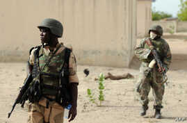 FILE - Nigerian soldiers are seen on patrol near a Boko Haram camp in the north of Borno state.