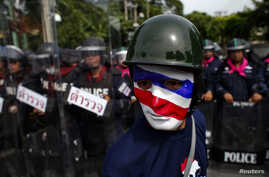 An anti-government protester wearing a mask painted in the colors of the Thai national flag looks on as riot police officers stand guard outside the parliament in Bangkok August 7, 2013. Thailand's parliament was due to debate a political amnesty bil