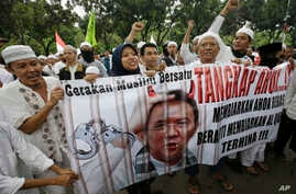 """Indonesia Protest: In this Friday, Oct. 14, 2016, photo, Muslim protesters hold a banner calling for the arrest of Jakarta's ethnic Chinese and Christian Governor Basuki Tjahaja Purnama, popularly known as """"Ahok"""", outside the City Hall. Indonesian po"""
