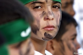 FILE - A Palestinian boy wears a headband with the logo of Hamas during a rally of the miltant Islamic group in the West Bank town of Bethlehem.