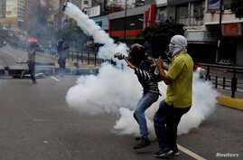 A demonstrator throws a tear gas canister during riots at a rally against Venezuelan president Nicolas Maduro's government in Caracas, Venezuela, June 7, 2017.