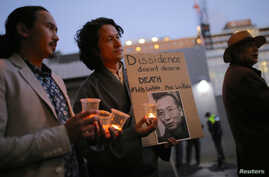 Members of the Australian Tibetan community stand together as they hold placards during a candlelight vigil for the Chinese Nobel Peace Prize-winning dissident Liu Xiaobo outside the Chinese embassy in Sydney, Australia, July 12, 2017.