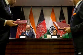 Afghanistan Foreign Minister Salahuddin Rabbani, sitting left and Indian External Affairs Minister Sushma Swaraj, sitting right, applaud during the exchange of agreements in New Delhi, India, Sept.11, 2017.
