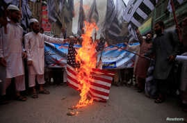 Supporters of the Jamaat-ud-Dawa Islamic organiztion burn a mock U.S. flag during a protest in Peshawar, Pakistan, May 27, 2016.