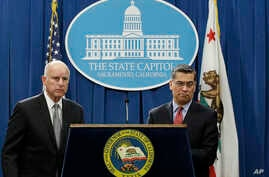 California Gov. Jerry Brown (L), accompanied by California Attorney General Xavier Becerra, listens to a question concerning remarks made U.S. Attorney General Jeff Sessions, March 7, 2018, in Sacramento, California.