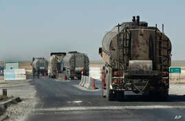 A convoy of oil trucks passes a Kurdish police (Assayesh) checkpoint, as they transport fuel produced in Kurdish-held areas in the east to other areas controlled by the same U.S-backed group to the west, on a highway in Hassakeh province, Syria, Apri