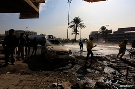People gather at the site of car bomb attack in Baghdad, January 15, 2014.