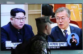 A South Korean marine passes by a TV screen showing file footage of South Korean President Moon Jae-in and North Korean leader Kim Jong Un, left, during a news program at the Seoul Railway Station in Seoul, South Korea, April 18, 2018.