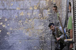 FILE - In this Monday Sept. 24, 2012 file photo, A Free Syrian Army soldier, right, looks through a mirror which helps him see Syrian troops from the other side, as he takes his position with his comrade during fighting, at the old city of Aleppo cit