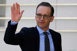 FILE - German Foreign Minister Heiko Maas waves upon his arrival to meet with Palestinian President Mahmoud Abbas meets in Ramallah, in the occupied West Bank, March 26, 2018.