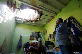 People check the damage after debris from ballistic missiles fired by Yemen's Houthi militia fell onto a house in Riyadh, Saudi Arabia, March 26, 2018.
