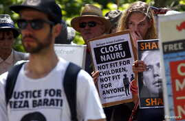 Protesters react as they hold placards and listen to speakers during a rally in support of refugees in central Sydney, Australia, Oct. 19, 2015.