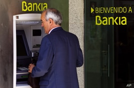 A man uses an ATM cash point machine at a branch of the Bankia bank in Madrid, May 18, 2012.