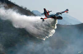 In this photo provided by the Santa Barbara County Fire Department, a Bombardier 415 Super Scooper makes a water drop on hot spots along the hillside east of Gibraltar Road in Santa Barbara, Calif., Dec. 17, 2017.
