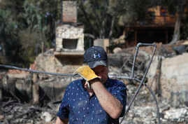 Roger Kelton, 67, wipes his tears while searching through the remains of his mother-in-law's home burned down by the Woolsey Fire, Nov. 13, 2018, in Agoura Hills, Calif.