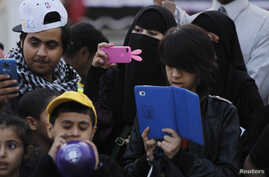 A family takes pictures with their mobile phones and tablet computer at the 27th Janadriya festival on the outskirts of Riyadh, Saudi Arabia, Feb. 13, 2012.