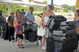 British tourists queue with their luggage to leave by charter flight from the international airport in Mombasa, Kenya after their government overnment warned its citizens this week to avoid the coastal city of Mombasa and beach towns nearby, May 16,