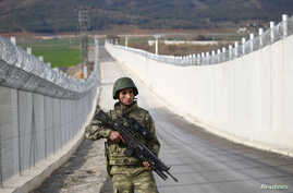 FILE - A Turkish soldier patrols along a wall on the border line between Turkey and Syria near the southeastern city of Kilis, Turkey, March 2, 2017.