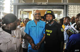 Former deputy governor of the Central Bank of Liberia Charles Sirleaf (C), the son of LIberia's former president Ellen Johnson Sirleaf, is escorted outside the City Court of Monrovia on March 4, 2019, where he appeared in court and charged with econo