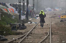 A migrant man walks on railway tracks with a towel on his head at the northern Greek border point of Idomeni, Greece, March 18, 2016.