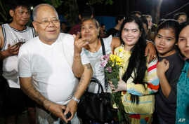 A prominent leader of Cambodia's land rights activist Tep Vanny, third from right, holds flowers as she celebrates upon the arrival at her home in Boeung Kak, in Phnom Penh, Cambodia, Aug. 20, 2018.