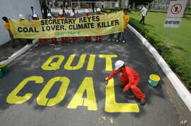 "FILE - Activists from the environmentalist group Greenpeace paint the words ""Quit Coal"" on the driveway of the Department of Energy at Manila's Taguig city Tuesday June 3, 2008 in another protest urging the Philippine Government to stop building and ..."