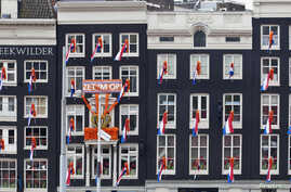 FILE - Dutch national flags hang from windows overlooking Central Station in Amsterdam, The Netherlands, April 28, 2013.