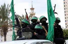 Masked militants from the Izzedine al-Qassam Brigades, a military wing of Hamas, ride vehicles as they commemorate the 30th anniversary of their group, in Gaza City,  Dec. 13, 2017.