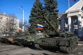Military vehicles, one flying a Russian flag, are seen parked in Perevalsk, eastern Ukraine, Nov. 5, 2014.