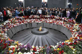 FILE -People lay flowers at a memorial to Armenians killed by the Ottoman Turks, as they mark the centenary of the mass killings, in Yerevan, Armenia, April 24, 2015.