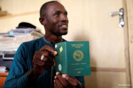 FILE - Abdul Giwa holds a copy of his passport during an interview with Reuters on the recent pronouncements of the Kaduna State government on the activity of the Shi'ite group in Kaduna, Nigeria  Nov. 2, 2016.