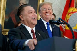President Donald Trump smiles at Broadcom CEO Hock Tan during an event to announce that the company is moving its global headquarters to the United States, in the Oval Office of the White House, Nov. 2, 2017.