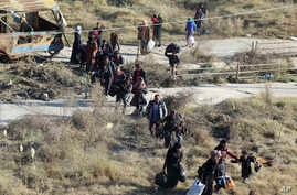 This photo provided by the Rumaf, a Syrian Kurdish activist group, which has been authenticated based on its contents and other AP reporting, in a Sunday, Nov. 27, 2016 photo, shows people fleeing rebel-held eastern neighborhoods of Aleppo into the S