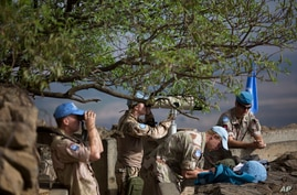 FILE - U.N. peacekeepers from the United Nations Disengagement Observer Force, also known as UNDOF, observe Syria's Quneitra province at an observation point on Mt. Bental in the Israeli-controlled Golan Heights, overlooking the border with Syria, Fr