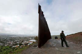 Border Patrol agent Vincent Pirro walks near where the border wall ends that separates Tijuana, Mexico, left, from San Diego, right, Feb. 5, 2019, in San Diego.