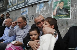 Senior Hamas leader Ismail Haniyeh kisses the son of Hamas military chief, who was killed by an Israeli air strike, as he consoles the family in Gaza City November 22, 2012.