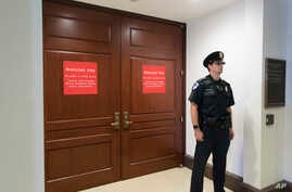 In this July 25, 2017 photo, a U.S. Capitol Police office stands guard outside a secure area in the basement of the Capitol in Washington, where the House Intelligence Committee has been conducting interviews.