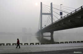 A resident walks along a street on the banks of the Songhua River near a highway bridge on a hazy day in Jilin province, Feb. 25, 2014.