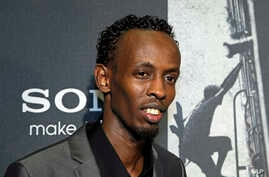 """Barkhad Abdi poses for photographers as he walks the red carpet at a screening for the movie """"Captain Phillips"""" at the Newseum in Washington, Oct. 2, 2013."""
