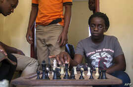 18-year-old Phiona Mutesi plays a game of chess with her colleagues at the chess academy in Kibuye, Kampala, Jan. 26, 2015.