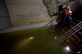 Joseph Leader, Metropolitan Tranportation Authority Vice President and Chief Maintenance Officer, shines a flashlight on standing water inside the South Ferry 1 train station in New York City, Oct. 31, 2012.