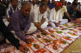 Indian businessmen write religious verses on their record-keeping books as part of a ritual to worship the Hindu deity of wealth Goddess Lakshmi on Diwali, the Indian festival of lights, in the western Indian city of Ahmedabad November 3, 2013. The r