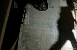 A shadow of a migrant enforcement officer is cast on a makeshift shelter, built by suspected illegal migrant workers, as he tries to break a locked door during a crackdown on illegal migrant workers in Nilai, outside Kuala Lumpur September 1, 2013.