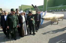 FILE - President Hassan Rouhani, center, and Iran's Defense Minister Hossein Dehqan, second right, visit Iran's defense capabilities exhibition in Tehran, Aug. 24, 2014.