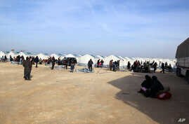 In this photo provided by Turkey's Islamic aid group of IHH, Syrians fleeing conflict in their country's Azaz region, are seen at a temporary accommodation center set up by the group near the Bab al-Salam border crossing, Syria, Feb. 5, 2016.