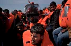 In this April 6, 2017 file photo, migrants are rescued from a rubber boat by members of Proactiva Open Arms NGO, in the Mediterranean sea, about 56 miles north of Sabratha, Libya. With the Greek smuggling route largely closed off, the path of least r